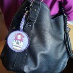 Maatuska-kangasmerkki avaimenperäksi tehtynä hienolla helmikirjonnalla, laitettuna laukkua somistamaan.
